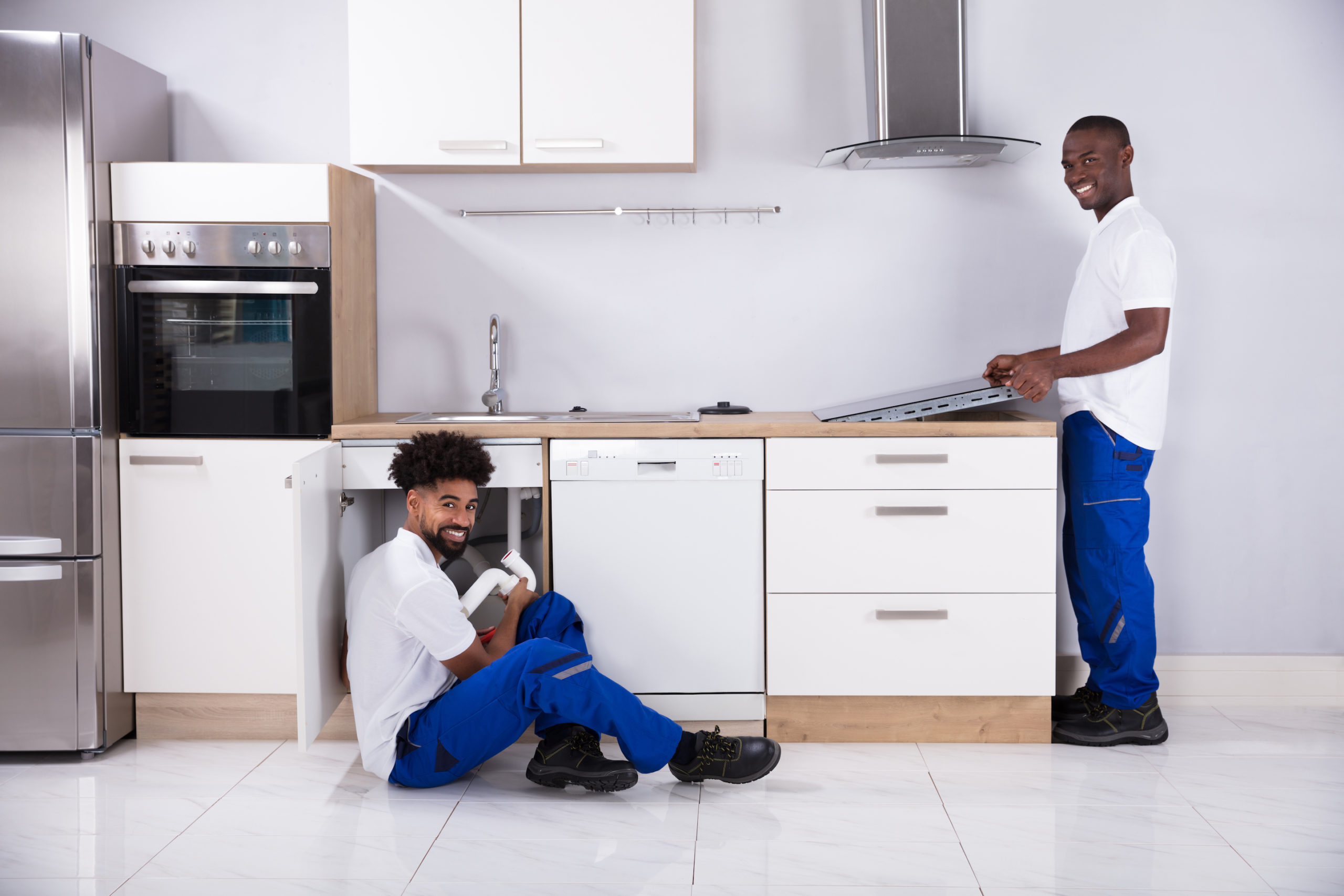 Rear View Of Two Young Service Men In Uniform Assembling Kitchen